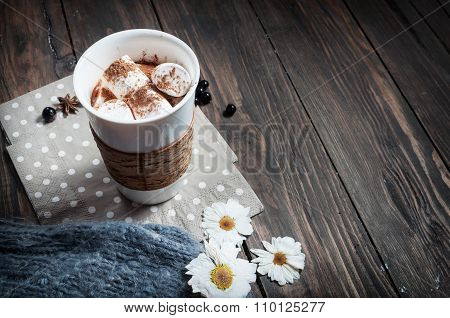 Hands in knitted mittens holding hot chocolate with marshmallow