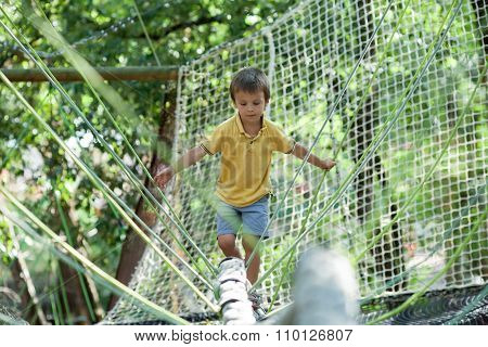 Cute Child Climbing In A Rope Playground Structure