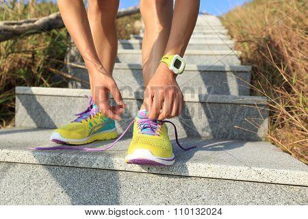 young woman runner tying shoelace