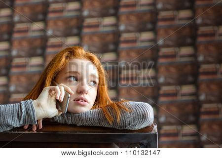 Pretty cute lovely girl with red hair talking on mobile phone and looking away
