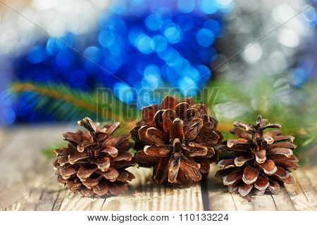 Pine Cones On Wooden Board Against Christmas Bokeh Background