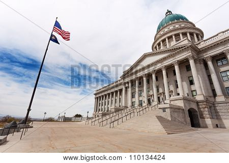 Utah Capitol building with American flag on sky