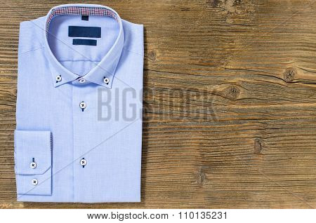 Blue casual shirt over wooden background. Top view