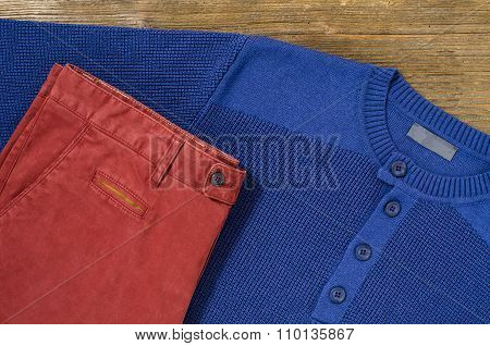 Trousers and sweater on wooden table