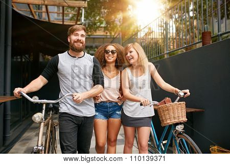 Young Friends With Their Bike On City Street