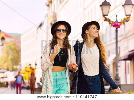 Two charming young women walking together smiling