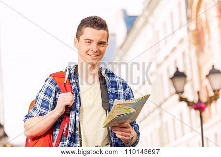 Boy with rucksack and city map on the street