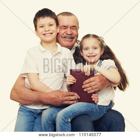 Grandfather and grandchildren read book on white