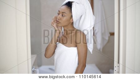 shot of a young african american woman looking on the mirror after shower and smiling