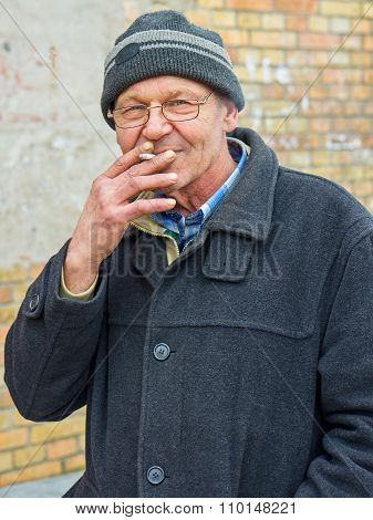 Elderly Man Enjoying A Cigarette Outside