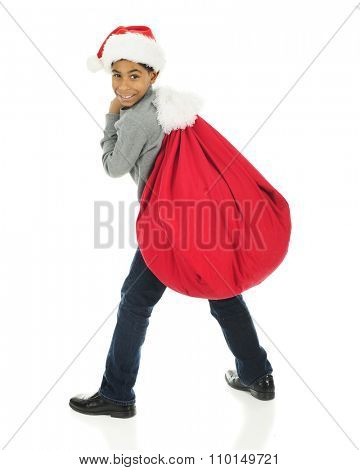 An elementary boy looking over his shoulder at the viewer as he hauls Santa's sack on his back.  On a white background.