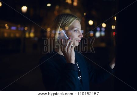 Girl touching digital display on bus stop during mobile phone conversation