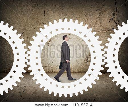 Man walking in cog wheel