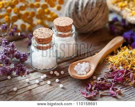 Bottles Of Homeopathy Globules, Wooden Spoon And Dry Healthy Herbs.