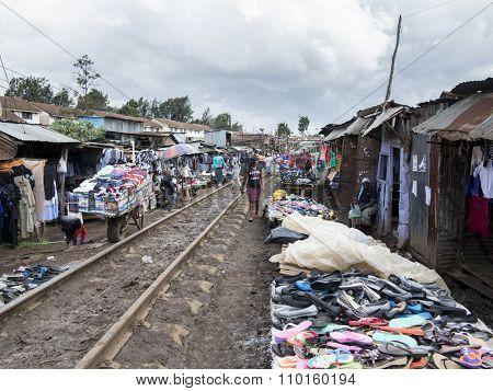 KIBERA, KENYA-NOVEMBER 5, 2015: Unidentified merchants and buyers work along the tracks in Kibera, the largest urban slum in Africa.