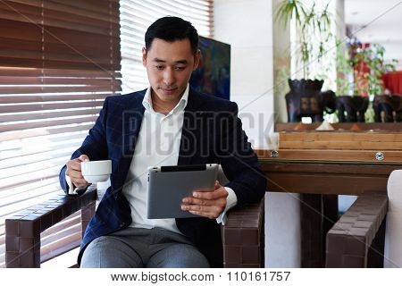 Male purposeful economist watching news on digital tablet while sitting in modern interior