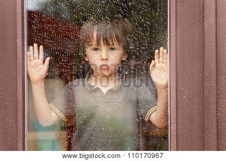 Little Boy Behind The Window In The Rain