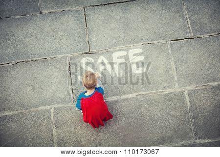 Little boy draws inscription outdoors