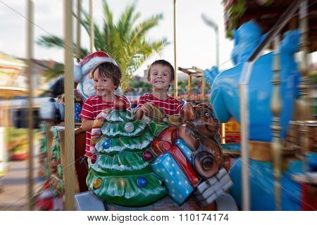 Sweet Boys, Brothers, Riding In A Santa Claus Sledge On A Merry-go-round