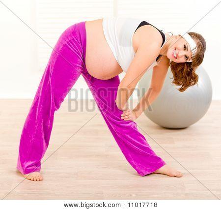 Lächelnd schöne schwangere Frau, die Übungen zu Hause