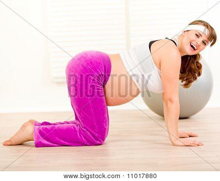 Smiling beautiful pregnant woman making gymnastics at living room