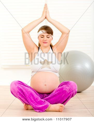 Beautiful pregnant woman doing yoga on floor at living room