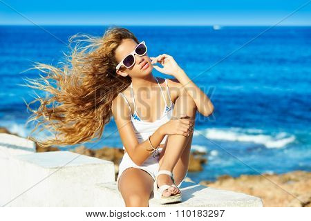 Blond kid teen girl on the beach long with curly hair waving at wind