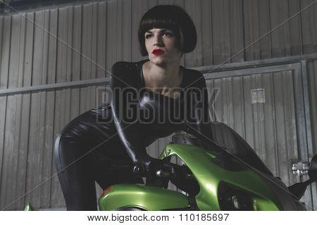 motor, brunette with latex suit mounted on a bike with a modern design