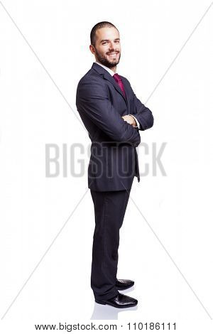 Smiling young businessman standing with arms crossed on white background
