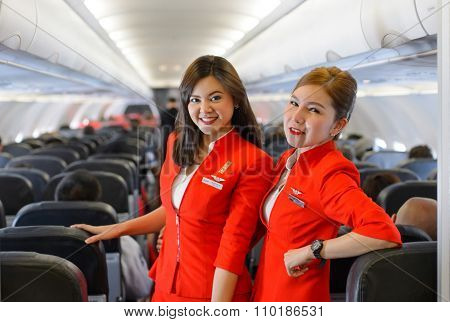SINGAPORE - NOVEMBER 04, 2015: AirAsia crew member on board of Airbus A320. AirAsia is a Malaysian low-cost airline headquartered near Kuala Lumpur, Malaysia