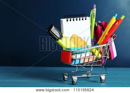 Bright stationery objects in mini supermarket cart on chalkboard background