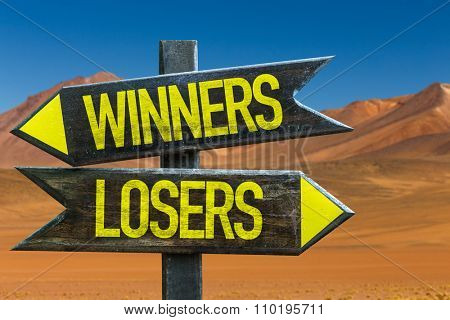 Winners - Losers signpost in a desert background