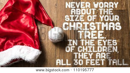 Never Worry About the Size of Your Christmas Tree. In The Eyes of Children They Are All 30 Feet Tall written on wooden with Santa Hat