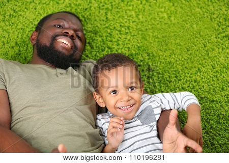 Father and son playing on green carpet