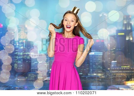 people, holidays and fashion concept - happy young woman or teen girl in pink dress and princess crown over night city and holidays lights background