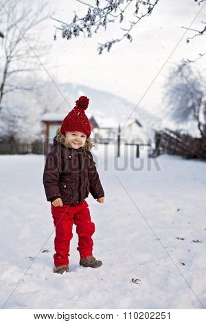 Portrait Of Child In Brown Jacket And Red Knitted Hat And Red Trousers, Lots Of Snow. Winter Forest.