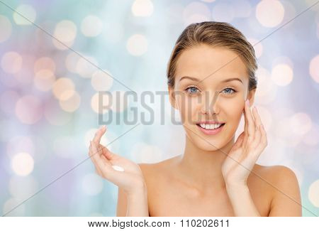 beauty, people, cosmetics, skincare and health concept - happy smiling young woman applying cream to her face over blue holidays lights background
