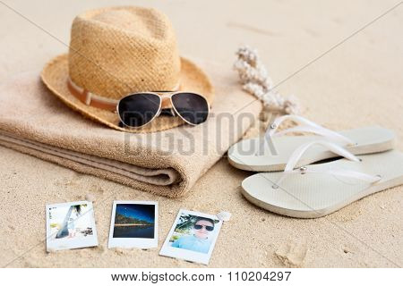Straw hat, towel, sun glasses, flip flops and instant photos on a tropical beach