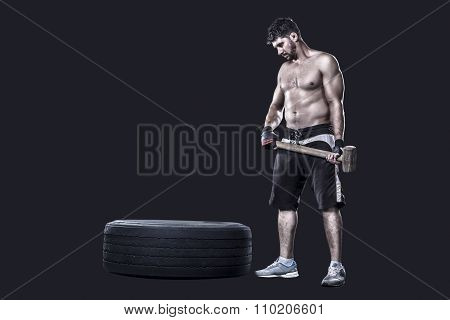 Sportsman with a sledgehammer next to tire isolated on black