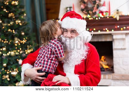 Santa Claus and child boy. Kid telling his Christmas wish in Santa Claus near the Christmas tree opp