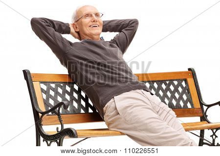 Relaxed senior gentleman sitting on a wooden bench and looking in the distance isolated on white background