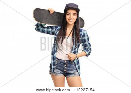 Hipster girl in blue checkered shirt holding a skateboard and looking at the camera isolated on white background