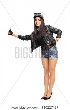 Full length portrait of a female biker in black leather jacket hitchhiking with her thumb isolated on white background