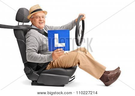 Senior gentleman sitting on a car seat and holding an L-sign isolated on white background