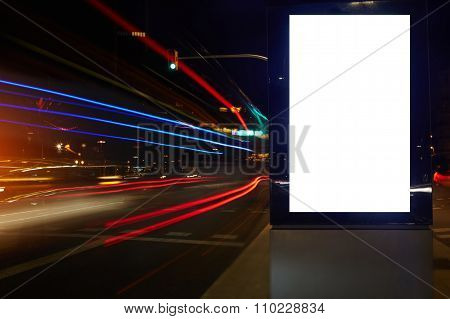 Public information board in night city with shutter speed on background