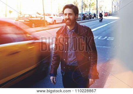 Happy cheerful hipster man with cool trendy look standing in urban setting