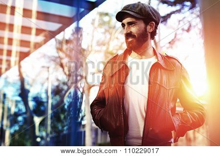Beautiful male with trendy look standing in urban setting in autumn day