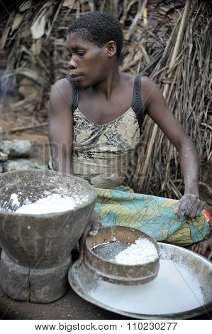 Jungle Of Car. Africa. Jungle Of The Central-african Republic. Baka Woman Cooks Food, Crushing A Flo