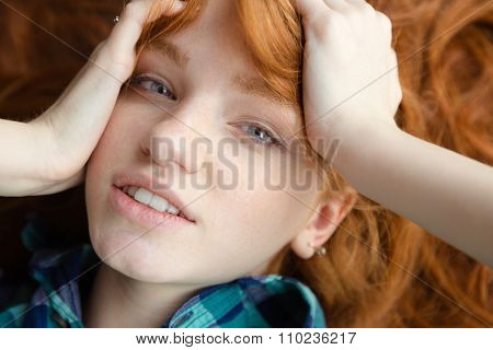 Closeup of lovely cute redhead girl in blue checkered shirt lying on the floor with tousled hair