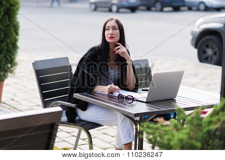 Dreamy woman sitting at the table with paper documents and laptop computer in sidewalk cafe